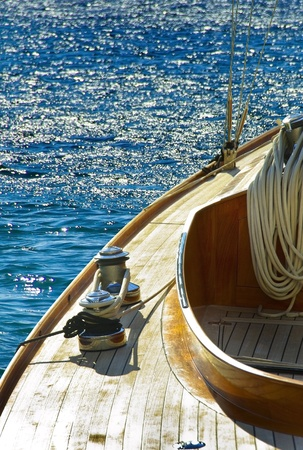 Wooden sailboat on the blue mediterranean sea  Details of a classic beautiful sailing yacht  with ropes, knots and wood plank on deck background  photo