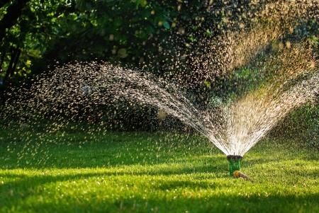 paisajismo: Moderno dispositivo de sistema de riego riego de jardines - t�cnica de riego en el jard�n de agua por aspersi�n del c�sped rociar sobre la hierba verde Foto de archivo