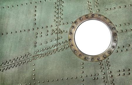 Marco de ojo de buey en el ojo de buey viejo avión - ventana de agujero blanco aislado en el fondo de metal con remaches Foto de archivo