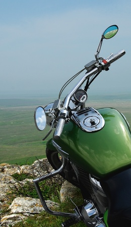 beautiful shiny green bike on the breakage of the mountain
