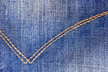 close button: Blue jeans with yellow stitches as a backdrop  Classical jeans texture  Close-up of denim indigo jeans background