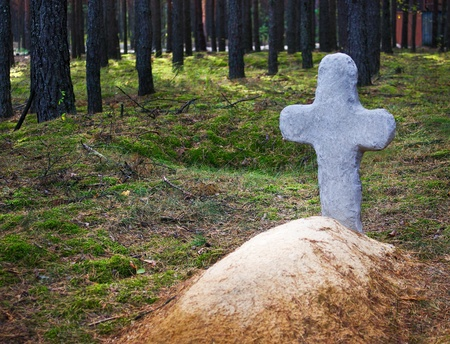 Tradition christians tombstone on the grave in the old cemetery  Fresh mound with a stone cross on the edge of the forest  photo