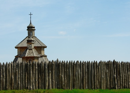stockade: palisade of historic fortress  and wooden church on sky background Stock Photo
