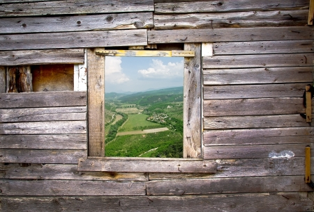 View from the old window - wooden frame of rural landscape  Window on the wooden wall with a farmland view  Countryside with green fields - view through the window on the wooden background
