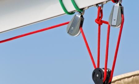 �ber Wasser: Segeln Takelage Blocks und rote Schn�re Detail der Yacht Seile von Segelboot - greift auf die Takelage Yacht Yachting Ausr�stung - Rollen-Bl�cke