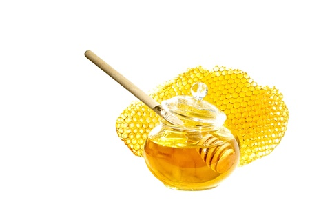 Pot of honey with stick and bee honeycomb isolated on white background   Honey spoon in glass jar and honeycombs wax  photo