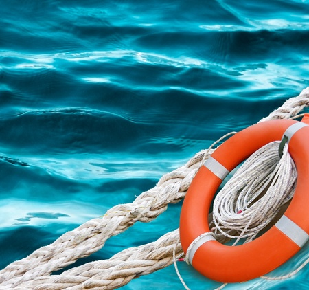 life preserver: Life ring on the blue sea water  Marine ropes and red lifebuoy - rescue tools concept