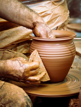 Potter hands with pottery wheel and clay pot photo