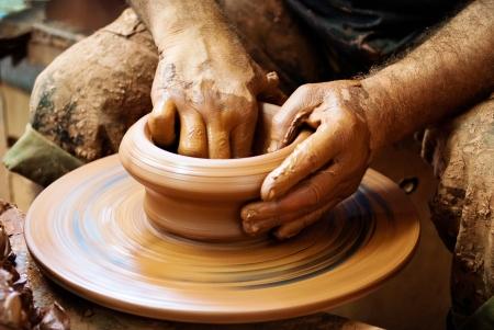 alfarero: Las manos de Potter decisiones en arcilla en la rueda de alfarería Foto de archivo