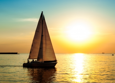 recreation yachts: Yacht sail against sun light  Holiday lifestyle on yacht during the sea sunset  Stock Photo