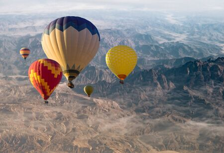Hot air balloons flying over mountains valley.