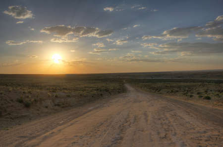 chaco: Sunset breaking through clouds over dirt road leading to Chaco Culture National Park  New Mexico, USA  Stock Photo