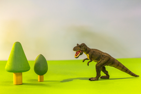 Toy dinosaur in a toy forest. like a real dino on a bright studio background with wooden trees.Eco toys.