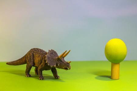 Toy dinosaur in a toy forest. like a real dino on a bright studio background with wooden trees. Eco toys. Stock Photo