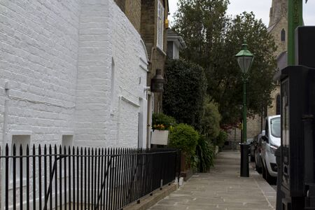 Pavement in a quiet area of London. Brick walls of houses. European style.