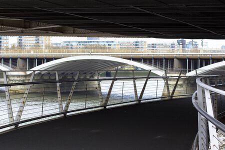 Under the Chelsea Bridge. View of the Thames and the railway bridge. Pedestrian bridge leading to Battersea Park. Stock Photo