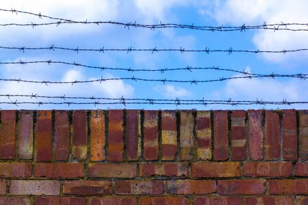 Barbed wire and brick wallagainst the blue sky. The blue sky is covered with barbed wire. Prison and blue cloudy sky. 스톡 콘텐츠