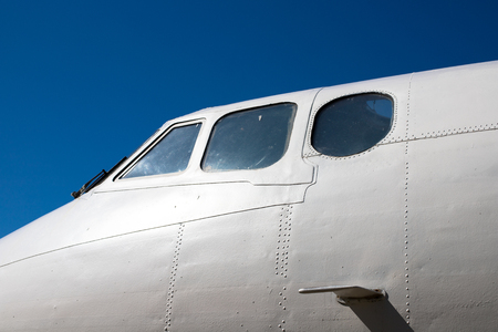 Fuselage cockpit. Part of the aircraft. The nose of the aircraft against the blue sky.