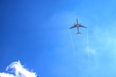 Airplan leaves a trail in the blue sky . Airliner is takking off. White cloud in the blue sky in which the plane flies.