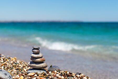 Pirámide de piedras. Obo de guijarros. Torre de piedra en la playa contra el mar azul. Equilibrio, tranquilidad, las piedras forman una pirámide en la playa de guijarros.