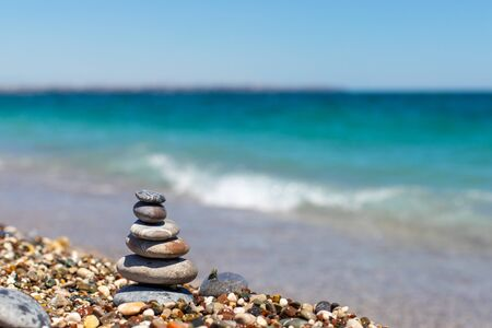 Piramide di pietre. Obo dai ciottoli. Torre di pietra sulla spiaggia contro il mare blu. Equilibrio, tranquillità, le pietre formano una piramide sulla spiaggia di ciottoli.