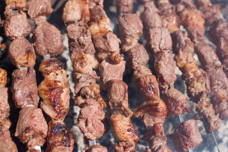 The texture of roasted meat. Appetizing cuts of meat on skewers. Grilled lamb, very tasty food. Kebab background.