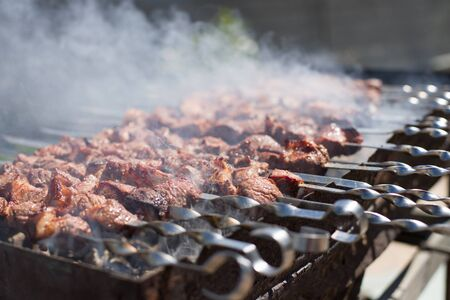 Meat with smoke on a barbecue grill over charcoal. Grilled cubes of meat on metal skewer. Meat on skewers is roasted on fire
