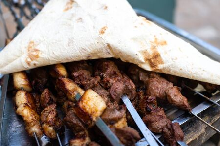 Roasted meat. Appetizing cuts of meat on skewers. Grilled lamb, very tasty food. Kebab background.