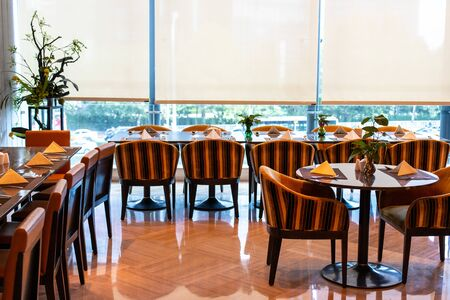 Served tables in the hotel restaurant. The banquet room is ready to receive guests. Roller blinds omitted and a Chinese plant in the corner. Stok Fotoğraf