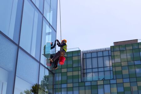 Window cleaner on high-rise buildings. Industrial climber. A man hangs on a building and washes windows. Stok Fotoğraf