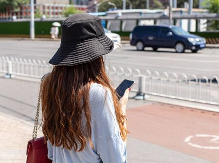 A Chinese woman in a sun hat stands on sidewalk and holds a smartphone. Portrait photo from behind, face is not visible and background is blurred.