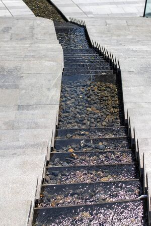 City stream. Water cascade. Steps down and in the middle, water flows down the steps. Modern designer steps Stock fotó
