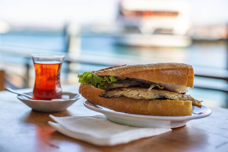Istanbul fish sandwich. Burger with fried fish. Turkish tea with Balik Ekmek. Blurred background with sea view