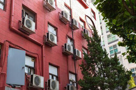 Immeuble de grande hauteur de la cour. La façade est faite de tuiles rouges, une porte en fer, un tuyau et des fils dépassent. Air conditionné au mur.