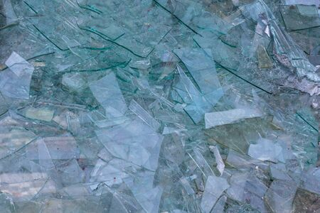 Broken glass texture and background. Ruined windows. Pile of large and small pieces of broken glass