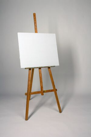 Blank canvas on Easel. Clean cloth stretched on subframe with copy space. Tripod for new oil painting Фото со стока