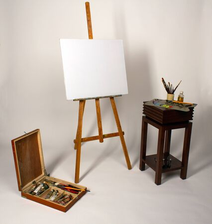 Oil painting. Blank canvas on Easel. Palette with paints and brushes. Squeeze out oil paints on a palette. Clean cloth with copy space. Set of brushes in a cup. Box with drawing tools 스톡 콘텐츠
