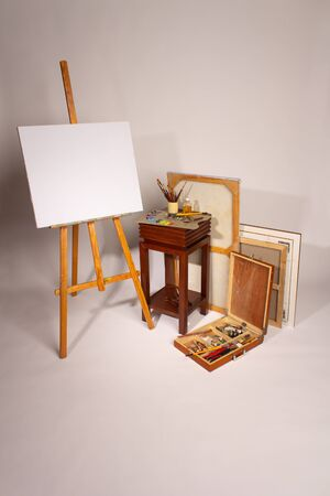 Oil painting. Blank canvas on Easel. Palette with paints and brushes. Squeeze out oil paints on a palette. Clean cloth with copy space. Set of brushes in a cup. Subframes and drawing tools 스톡 콘텐츠