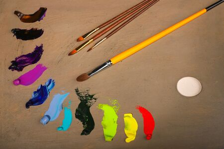 Oil painting. Palette with paints and brushes. The main tool of artist. Squeeze out oil paints on a palette