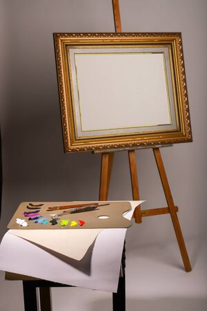 Oil painting. Easel and blank canvas. Palette with paints and brushes. Squeeze out oil paints on a palette and pieces of canvas. Clean canvas with copy space