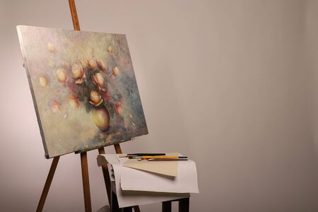 Easel with a painting and brushes nearby. Oil painting. Roses in a vase on canvas. Subframes and drawing tools with copy space