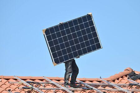 Joven técnico instalando paneles solares fotovoltaicos de energía alternativa Foto de archivo