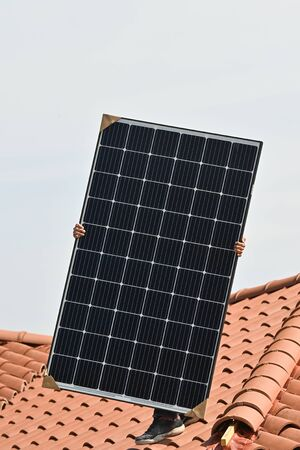 Young technician installing alternative energy photovoltaic solar panels