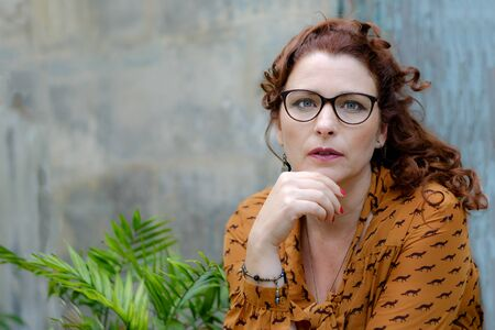 Close-up portrait of beautiful glamor senior woman in glasses outside