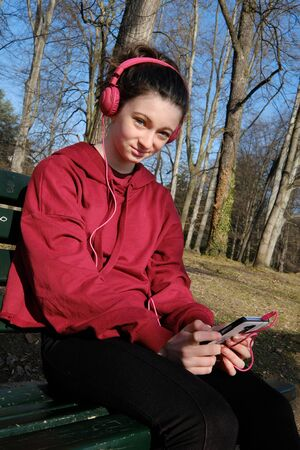 smiling teenager girl listen to music on a mobile in a forest park