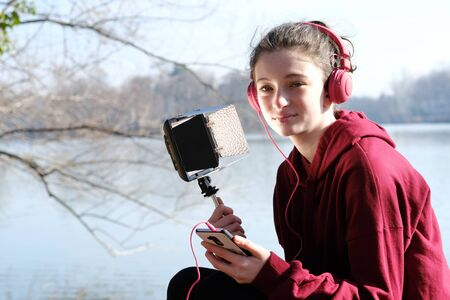 smiling teenager girl with pink headphoens listen to music on a mobile using a led light Stock Photo