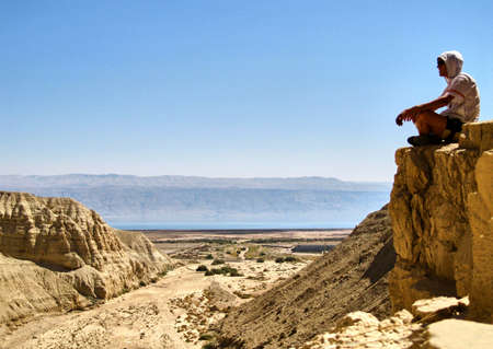 canyon negev: Man sits on a ledge. Canyon Ein Avdat in Negev desert. Israel.
