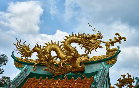 Gold dragon on a canopy. Chinese Temple. Koh Phangan Stock Photo