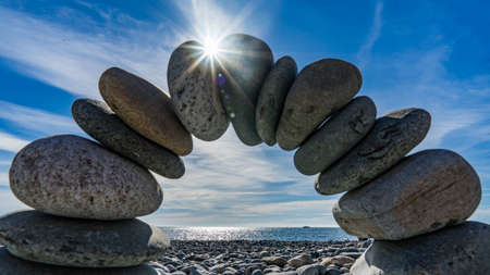 Stone arch on the shore of the Black Sea. Sun disk and blue sky on background, Sochi