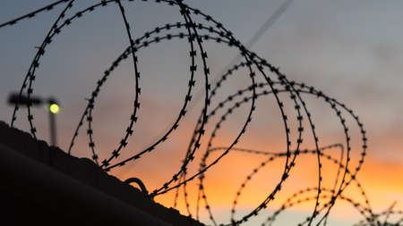 Sunset behind the barbed wire along the border. Sochi Stock Photo